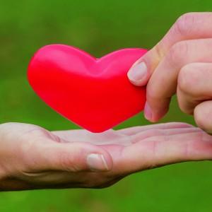 Die Hände eines Liebespaares halten ein Herz